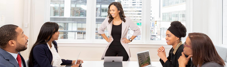 Smiling business woman explaining something to team mates